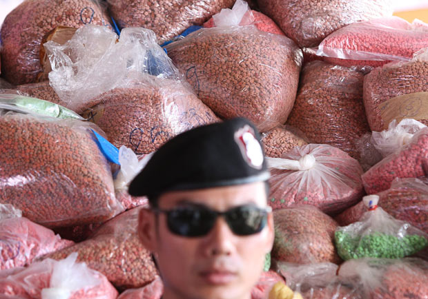 A Thai police officer keeps watch in front of bags of drugs before they were destroyed