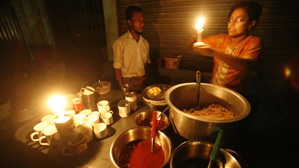 Street vendors work by candlelight. (PHOTO: Reuters)