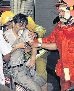 Rescue workers give first aid to a hotel guest injured in a fire at the eight-storey Grand Tower Inn Hotel on Charoen Nakhon Road in Khlong San district