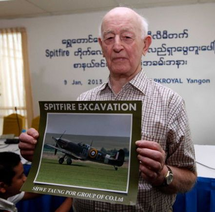 Stanley Coombe poses with a picture of a Spitfire fighter plane after a news conference at the Parkroyal hotel in Rangoon