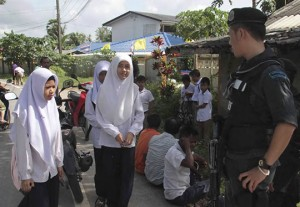 A soldier stands guard as students arrives at their school in Pattani province