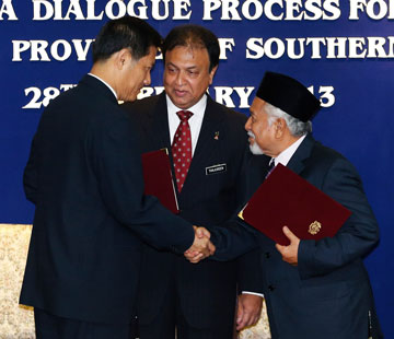 Secretary-general of Thailand's National Security Council, Paradorn Pattanathabutr (left), shakes hands with chief of Thailand's National Revolution Front (BRN) liaison office in Malaysia, Hassan Taib (right)