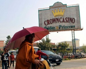 A Cambodian Buddhist monk takes a morning alms next to a casino signboard in Poipet,