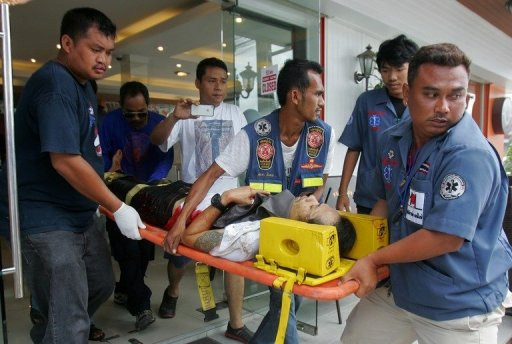 Rescuers carry out a man injured in a bombing in Thailand's Pattani