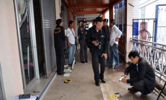 The alleged scene of the crime: Police comb the second-floor balcony of the building in Nakhon Si Thammarat, Thailand, where a British student was found weeping