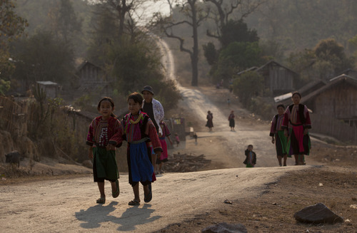 ethnic Lisu girls and women dressed in traditional clothing walk down a road in Thon Min Yar village, central Shan state, Myanmar.