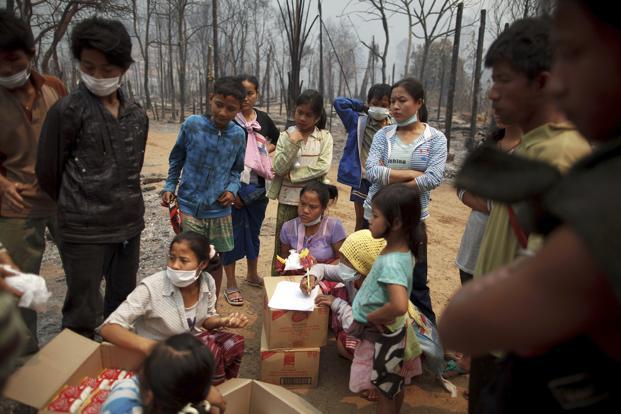 Survivors receive aid at the fire-gutted Ban Mae Surin refugee camp near Mae Hong Son on Sunday. Photo: Athit Perawongmetha/ Reuters