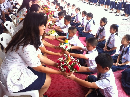 Thai students prostrate at the feet of their teachers in the annual Wai Khru Ceremony. In return the students receive a blessing.