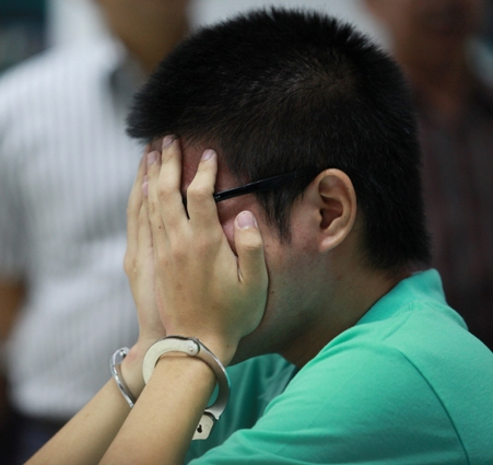 Murder suspect Mulyadi Budiman covers his face after being arrested at a Bangkok airport on Tuesday.