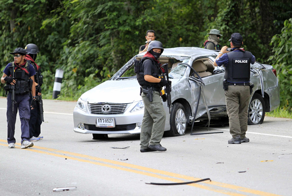 Security personnel inspect the site of the bomb attack on the car carrying Yala deputy governor Isra Thongthawat in Bannang Sata district of Yala on Friday.