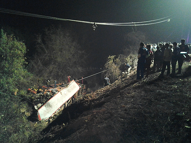 Rescue workers search for casualties around the wreckage of a bus accident in Phitsanulok province