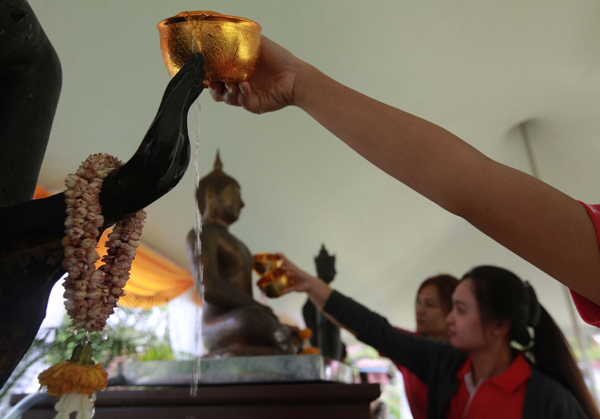 Young Thais pour water on a Buddha statue at a temple in Samut Prakan, hoping it will bring them good health and good fortune, during the traditional Thai New Year celebration, Songkran. (Photo by Somchai Poomlard)