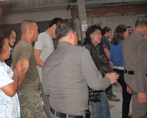 The man accused of holding three young women captive in Bangkok is led away by officials on Friday