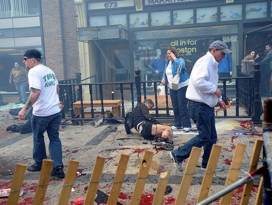 A man injured in an explosion at the 2013 Boston Marathon in Boston makes ... Bystanders help an injured woman at the scene of the first explosion