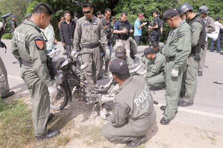 Thai bomb squad members inspect the wreckage of a motorcycle following a roadside bomb blast targeting a patrolling police truck by suspected separatist militants in Rangea