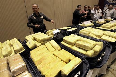 Thai police officers stand behind packs of methamphetamine on display at a news conference at police headquarters in Bangkok