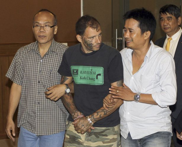 Enzo Gerber, center, of Switzerland, is escorted by plainclothes Thai police officers for a news conference at the Department of Special Investigation in Bangkok