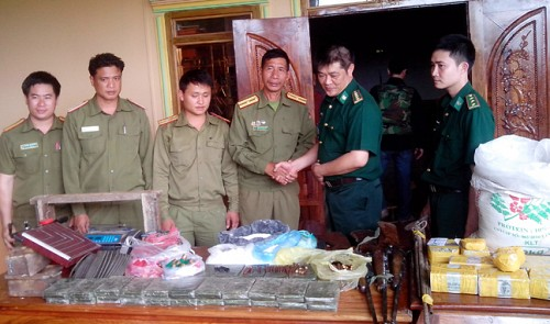 Officers of Laos and Vietnam stand by the drugs and weapons they have seized from three houses in Pa Hoc hamlet in Laos