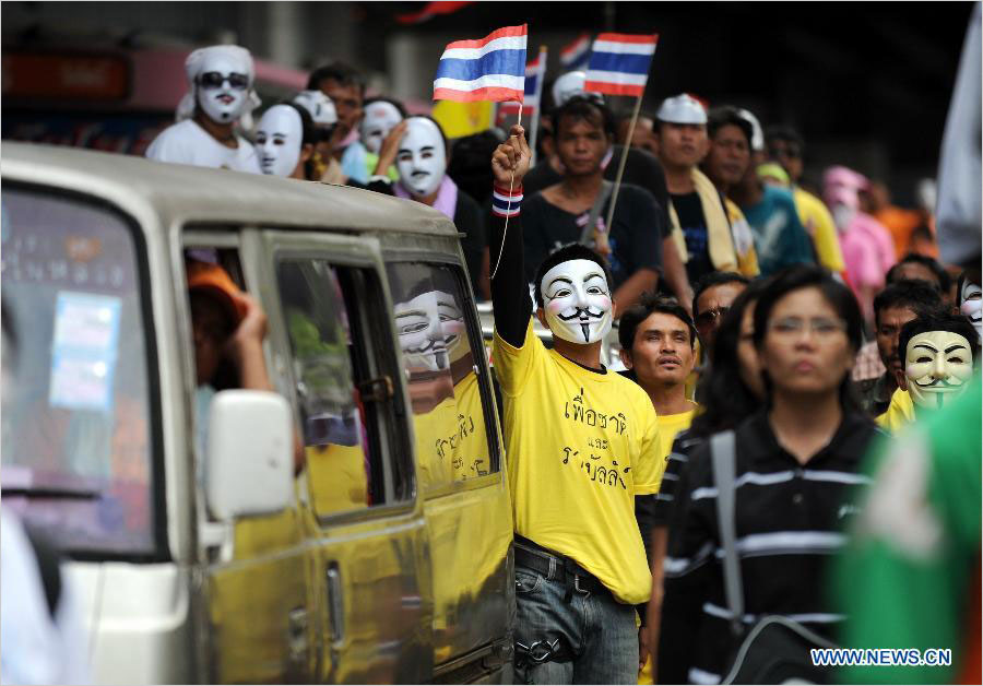 Protesters wearing masks shout slogans and hold up national flags as they stage an anti-government rally in a shopping district in Bangkok, capital of Thailand, on June 16, 2013. Thousands of protesters wearing masks held placards and shouted slogans against the government led by of Prime Minister Yingluck Shinawatra and her brother, former prime minister Thaksin Shinawatra.