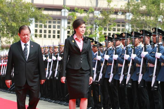 Prime Minister Yingluck Shinawatra, accompanied by Defence Minister Yuthasak Sasiprapha, yesterday reviews a guard of honour during her first official visit to the Defence Ministry.