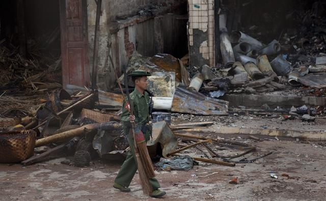 An army officer walks with brooms in front of a burned building that housed an orphanage for Muslim children in Lashio, northern Shan State, Myanmar Read more: http://www.theprovince.com/life/Deepseated+prejudice+radical+Buddhist+monks+fuel+violence/8461122/story.html#ixzz2UyKBoxYx