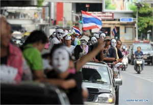 Protesters wearing masks shout slogans and hold up national flags as they march though a shopping district in Bangkok