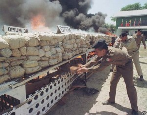 Burmese narcotic control officials put more wood to burn some six tons of seized opium, heroin and other drugs before diplomats, journalists and international business leaders in Rangoon, Burma
