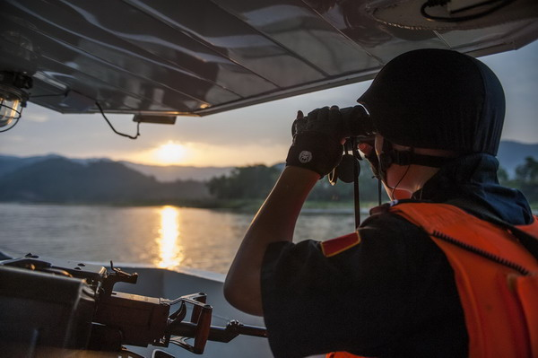 A Chinese patrolman looks through a telescope during a joint patrol by China, Myanmar, Thailand and Laos on the Mekong River in Jinghong city, Southwest China's Yunnan province