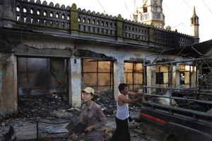 Ma Sandar Soe, left, salvages goods from her burned shop in the foreground of a vandalized mosque in Lashio, northern Shan State, Myanmar.