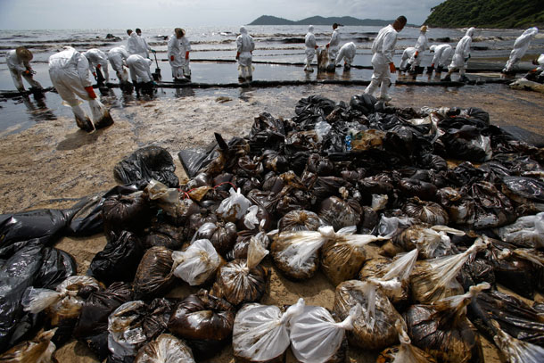 Thai soldiers in white biohazard suits take part in a clean up operation at Ao Prao Beach on Koh Samet