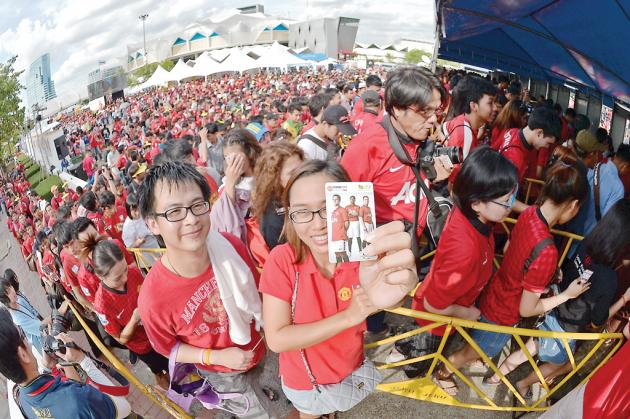 Red Devils fans stand in a queue at the entrance of Rajamangala National Stadium for the friendly match between the Singha All Stars and Manchester United.
