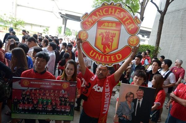 Manchester United fans hold posters as team players arrive at Don Muang International airport in Bangkok ahead of a July 13 friendly against a Thai All-Star XI as the club begins its new era under boss David Moyes.