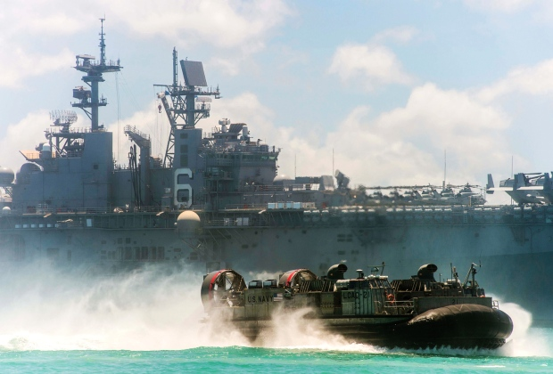 A landing craft air cushion hovers past the amphibious assault ship USS Bonhomme Richard near Okinawa on June 24, 2013. Between the Bonhomme Richard, the aircraft carrier USS George Washington and other ships, more than 10,000 sailors and Marines have deployed for patrols and exercises in the Western Pacific region during the past month.