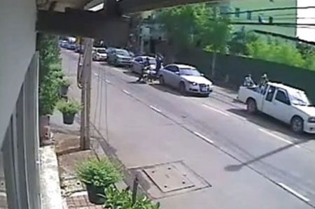 A motorcycle approaches at speed and the pillion passenger dismounts then humps a rock through his rear window.