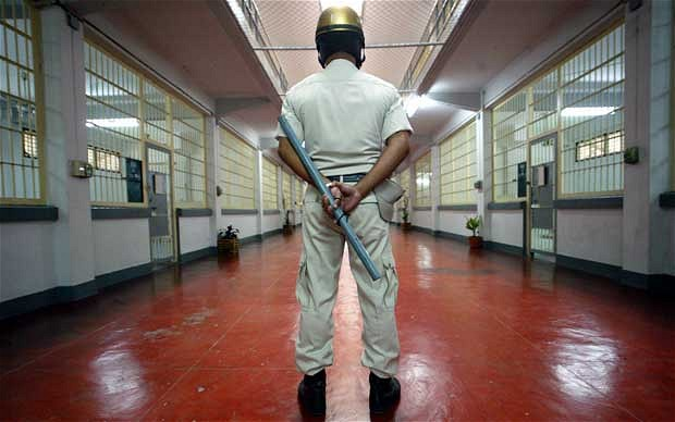 A prison guard with a baton in the sleeping quarters of Bangkok's Klong Prem prison  Photo: STEPHEN SHAVER/AFP/Getty Images