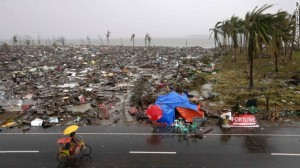 People ride past destruction in Tacloban