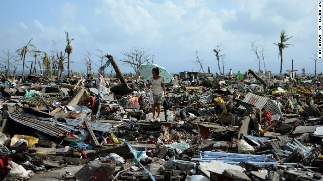 A surivor walks among the debris of houses destroyed by Super Typhoon Haiyan in Tacloban