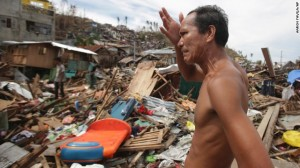 A man looks at his home destroyed by Typhoon Hayian in Tacloban, Philippines