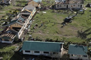 An aerial view shows damaged structures as residents unload relief goods from a helicopter after Typhoon Haiyan hit a village in Panay island in northern Iloilo Province, central Philippines November 9, 2013