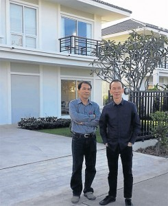 Mr Thanakorn (left) and Mr Sukit pose in front of a house at one of the company's projects. Property development is picking up steam ahead of an anticipated upswing in the border trade with Laos.