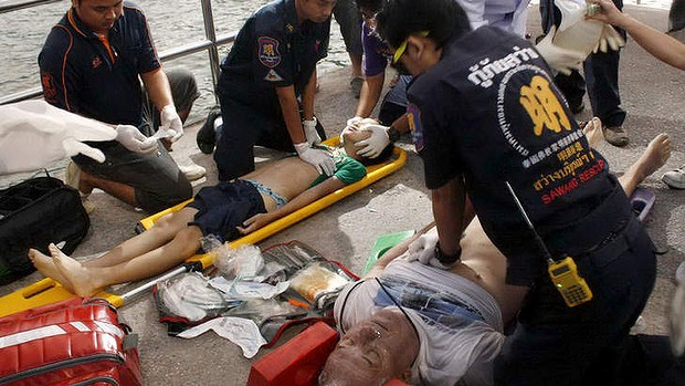 rescue workers and medics carry an injured tourist on a stretcher after a ferry sank at Pattaya
