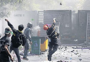 An anti-government Network of Students and People for Thailand's Reform protester throws a rock over Gate 1 of the Thai-Japanese StadiuminDinDaeng district duringclashes with police yesterday.