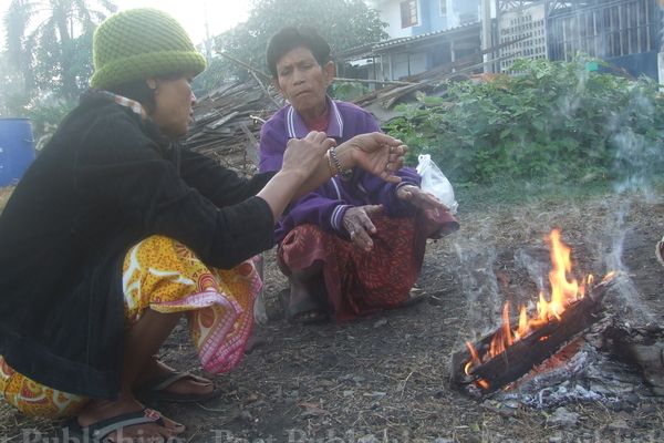 Villagers in Buri Ram province sit by the fire to keep themselves warm as cold weather hits the country. (Photo by Pikool Kaewhawong)