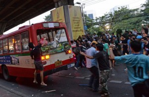 Thai opposition protesters attack a bus carrying pro-government Red Shirt supporters on their way to a rally at a stadium in Bangkok