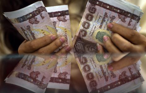 The baht may gradually weaken toward 32.9 per dollar as the political conflict threatens the economy