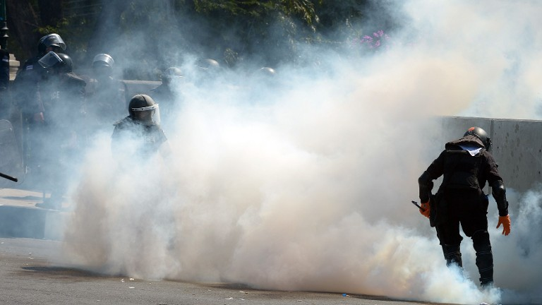 Thai riot policemen collect tear gas from anti-government protesters