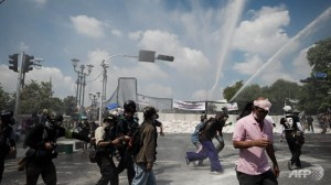 Thai police fired tear gas and water cannon at protesters trying to force their way into Government House