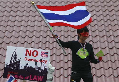 An anti-government protester waves a Thai national flag as he stands on a rooftop during a rally outside the Government House in Bangkok
