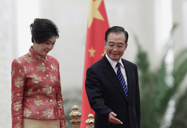 China's Premier Wen Jiabao shows the way to Thai Prime Minister Yingluck