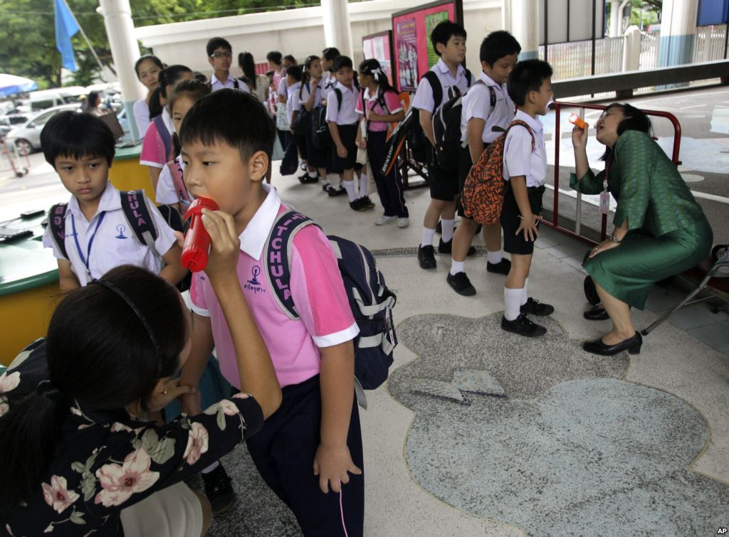 Thai teachers check the mouth of the students for hand, foot and mouth disease, before they get inside the school